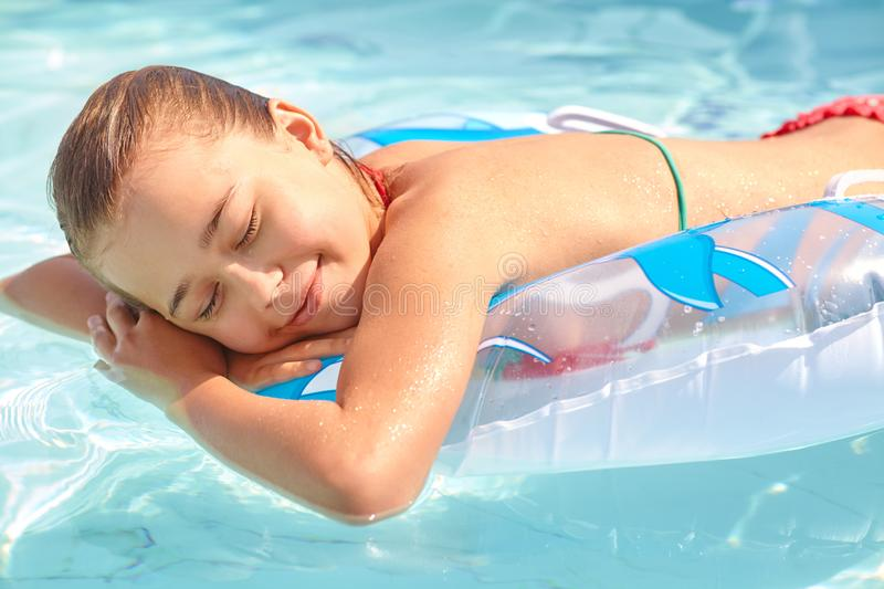 Relaxing girl in inflatable swimming circle in swimming pool. Relaxing girl in inflatable swimming circle in a swimming pool royalty free stock images