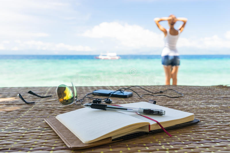 Relaxing girl, opened empty notepad is on the table with sunglasses, phone and headphones at the tropical sea background. Relaxing girl staying on the beach royalty free stock photography