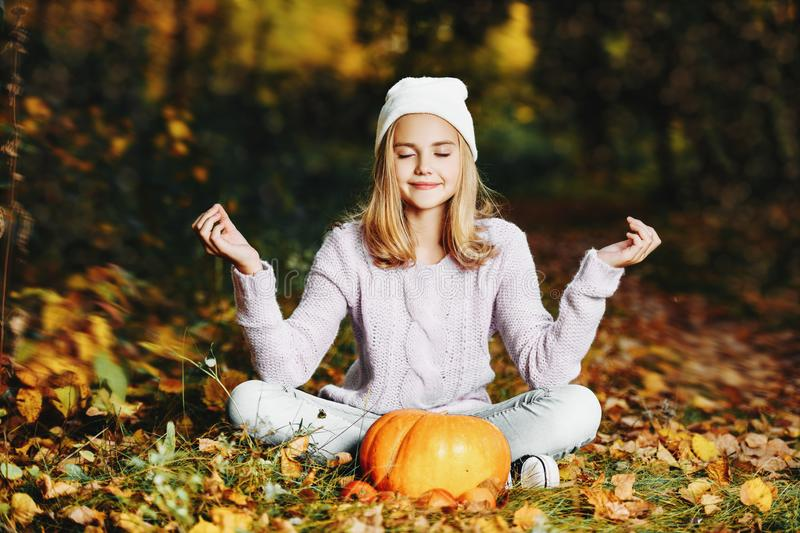 Relaxing on the ground. A pretty young girl is sitting on the ground with a pumpkin. Autumn fashion, beauty royalty free stock photography