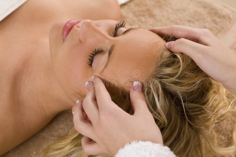 Relaxing Head Massage. A young blond woman receiving a relaxing head massage from a beauty therapist stock photos