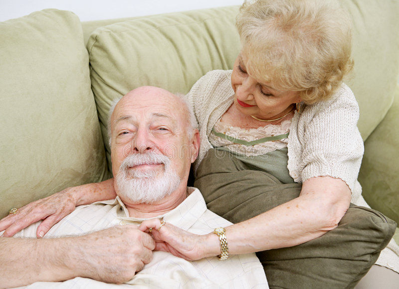 Relaxing at Home. Senior couple relaxing at home on the couch together stock photography