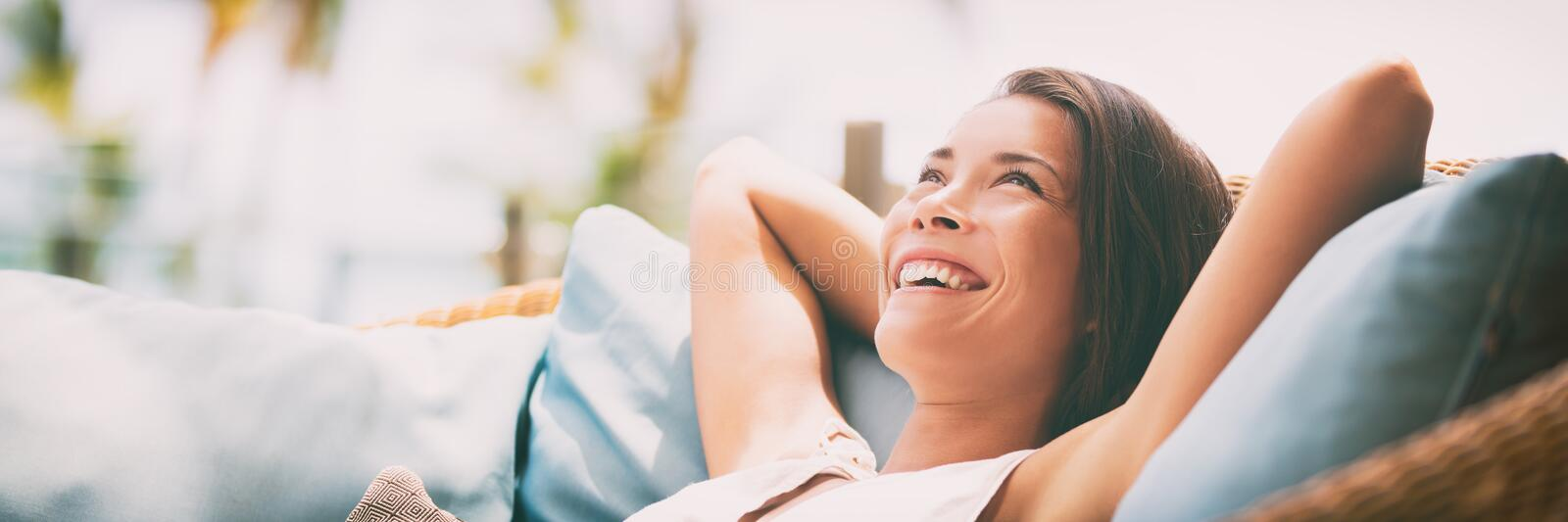 Relaxing home lifestyle happy woman in relax luxury hotel room sofa lying back with arms behind head smiling. Asian girl in. Comfortable lounging chair travel stock photo