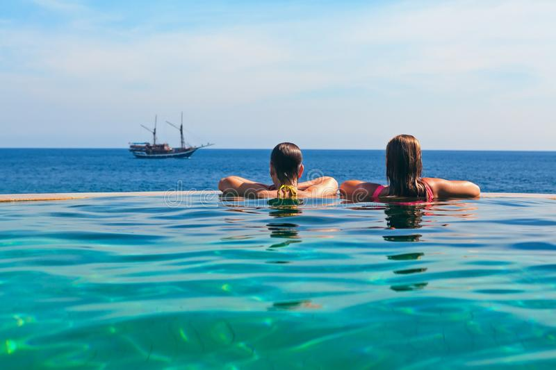 Relaxing in infinity swimming pool with sea view. Happy young women on summer beach holiday relaxing in luxury spa resort in infinity swimming pool with sea view stock photos