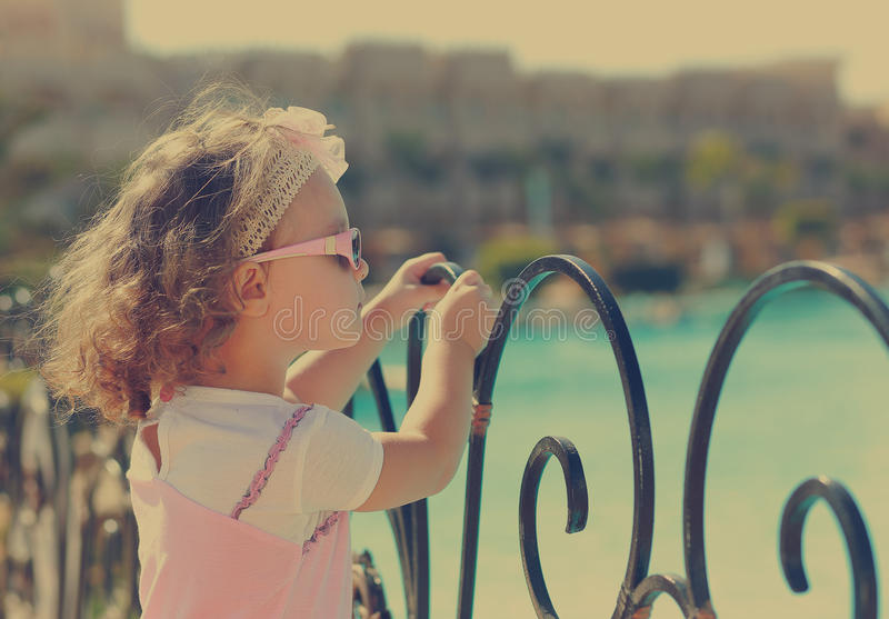 Relaxing kid girl looking on. The sea holding the fence royalty free stock photography