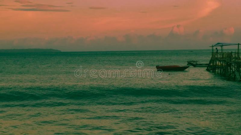 Beautiful landscape of lake for relaxing. Relaxing landscape. The boat of the fishermen who are in the ocean off at sunset stock image