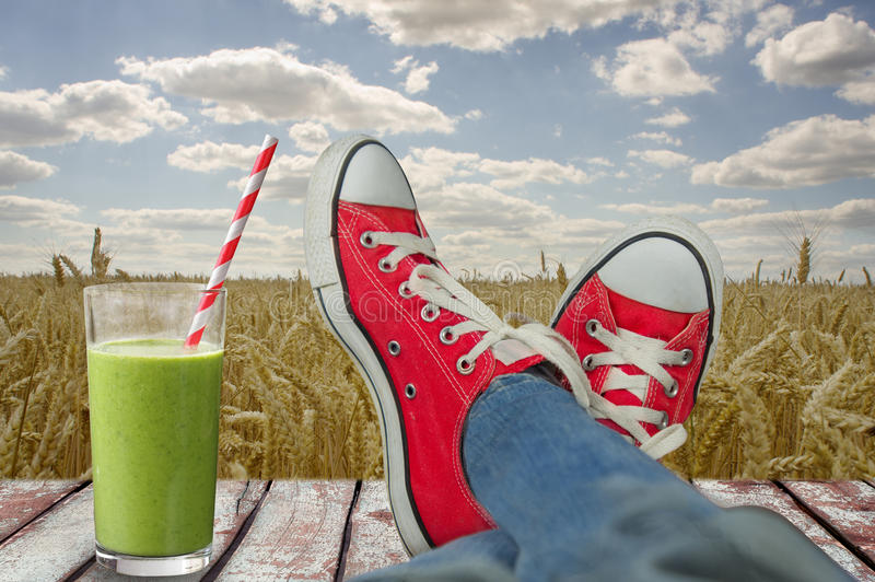 Relaxing landscape overlooking the wheat field with a refreshing. Glass of juice stock photo