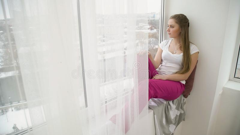 Relaxing leisure young pensive girl look window. Relaxing leisure. young pensive thoughtful teen girl sitting on the windowsill and looking out of the window royalty free stock photography