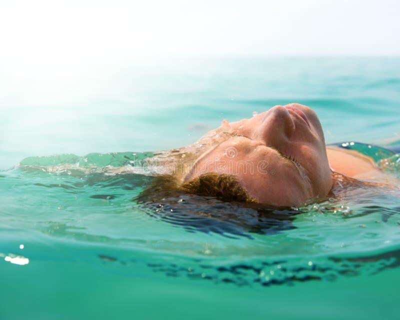 Relaxing man in ocean stock photo