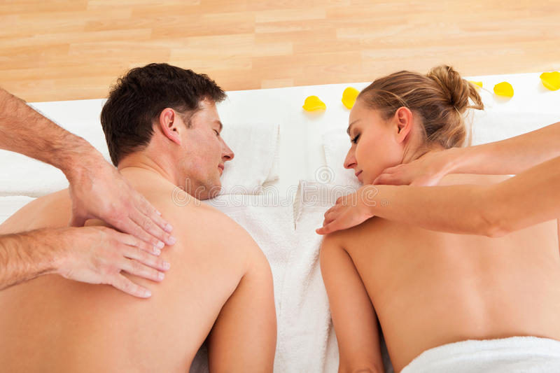 Relaxing massage for two. Young couple relaxing and enjoying a joint back massage at a spa and the women is surrounded by yellow flower petals stock image