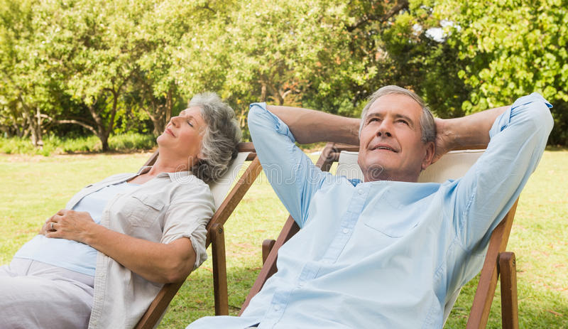 Relaxing mature couple sitting on sun loungers royalty free stock photos