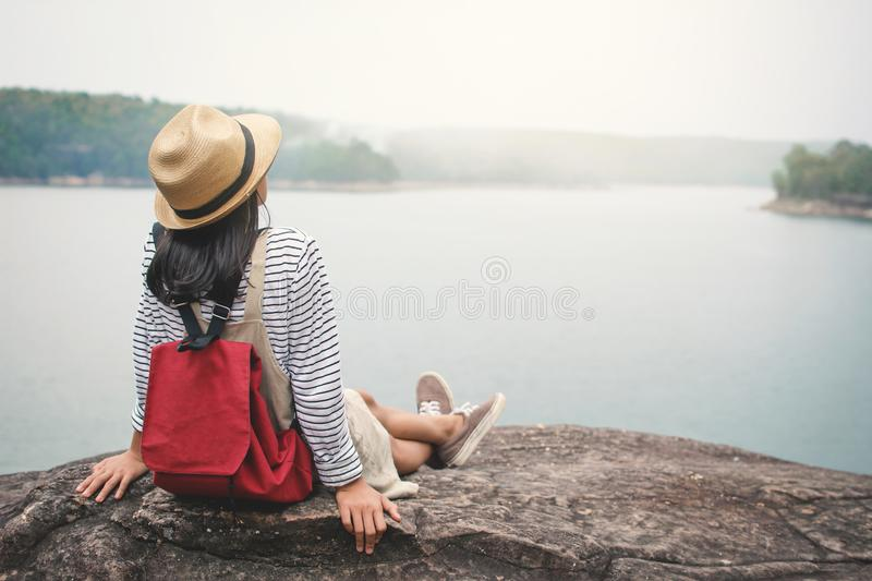 Relaxing moment Asian girl backpacker in nature. Enjoying time on holiday concept ,color of vintage tone selective and soft focus royalty free stock image