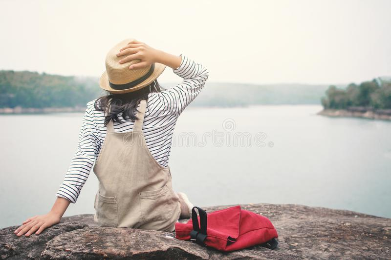Relaxing moment Asian girl backpacker in nature. Enjoying time on holiday concept ,color of vintage tone selective and soft focus stock photo