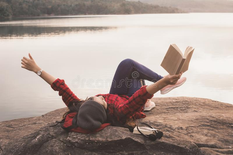 Relaxing moment Asian tourist reading a book on rock royalty free stock images