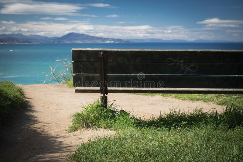 Relaxing moments, close up of bench with panoramic view on atlantic ocean, bidart, france stock photography