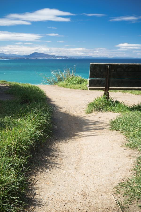 Relaxing moments, close up of bench with panoramic view on atlantic ocean, bidart, france royalty free stock image
