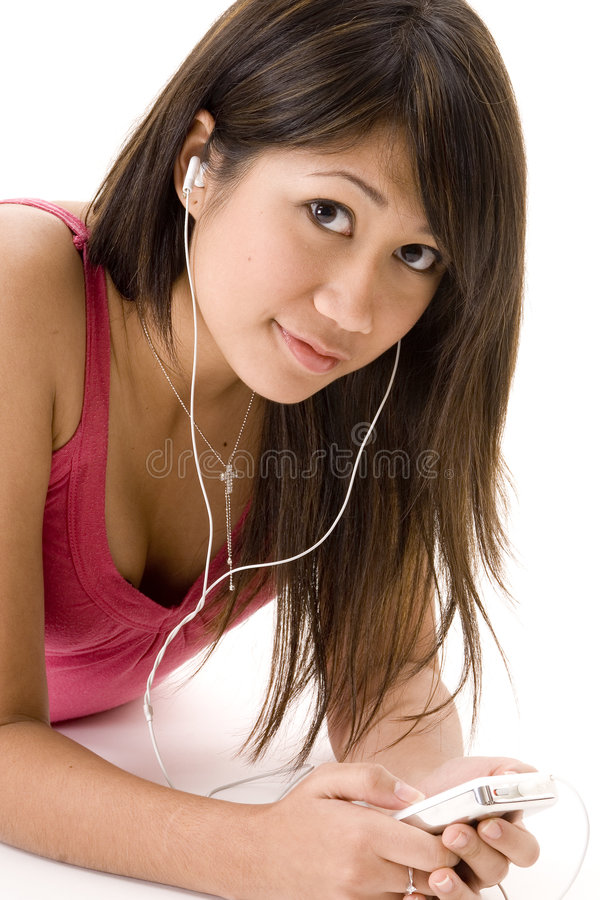 Relaxing With Music 6. A pretty young woman lying on the floor listening to music stock images