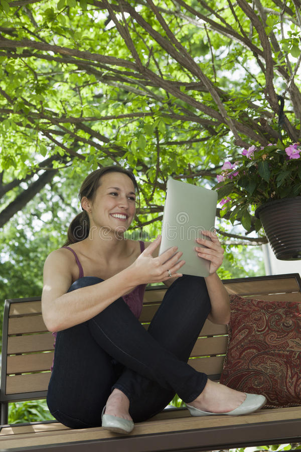 Relaxing outside reading a digital tablet royalty free stock image