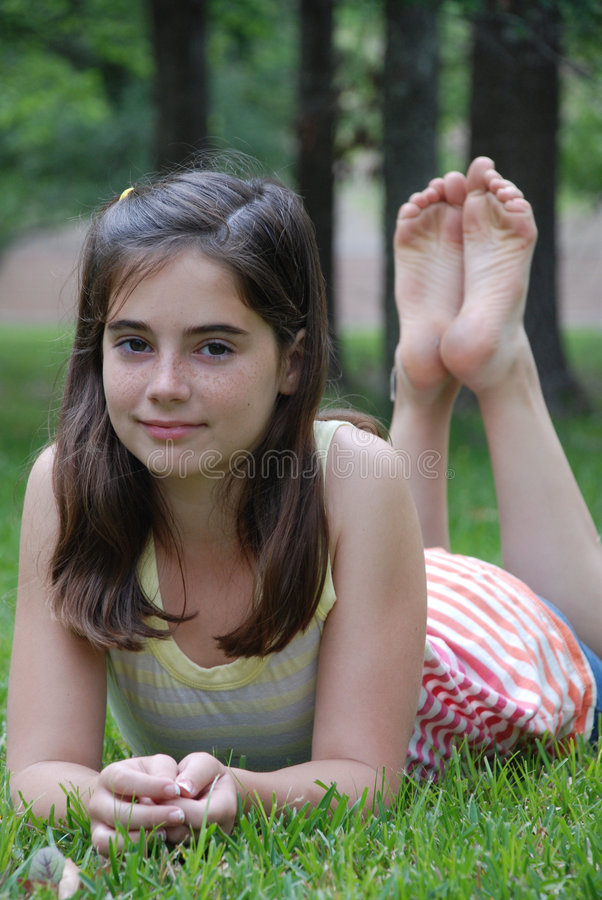 Relaxing in the park. Beautiful young tween relaxing and posing in the park with her feet up royalty free stock image