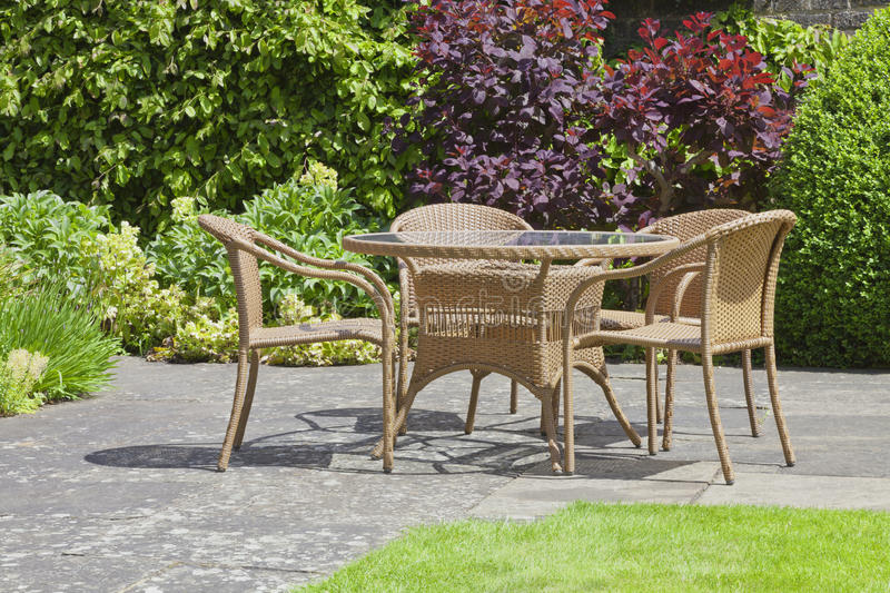 relaxing patio wicker chairs round table in a patio summer garden
