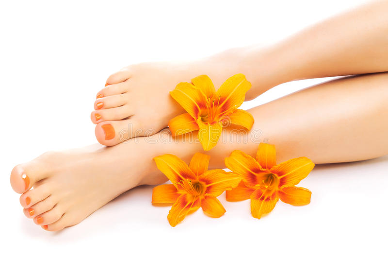 Relaxing pedicure with a orange lily flower royalty free stock photography