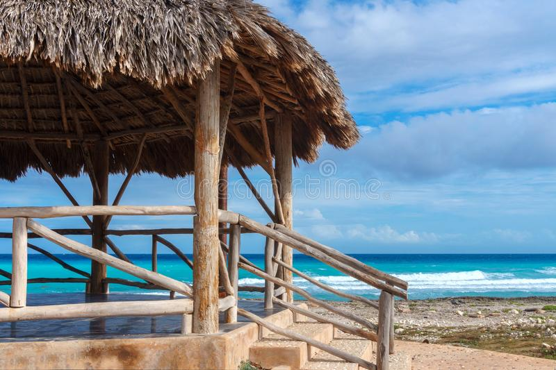 Gazebo or bungalow with a thatched roof on the Caribbean beach royalty free stock image
