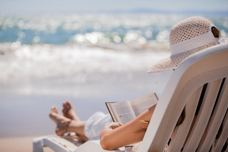 Relaxing and reading at the beach. Young woman on holidays relaxing on a chair in front of the ocean while reading a book stock image