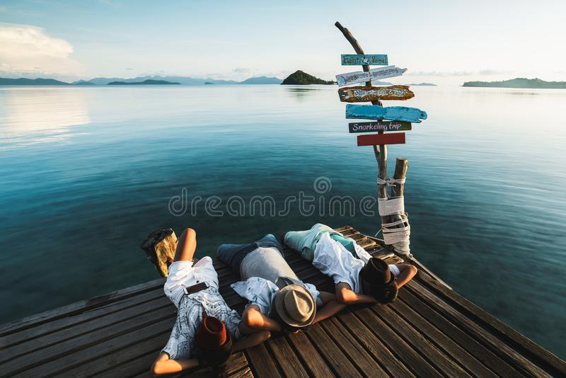 Relaxing. Relaxed outdoor portrait of happy young asian family resting on deck near the sea, Koh Mak Thailand royalty free stock images