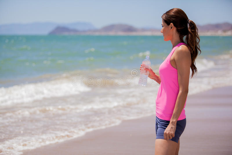 Relaxing after running at the beach. Pretty Hispanic brunette taking a break from running and drinking water from a bottle stock photos