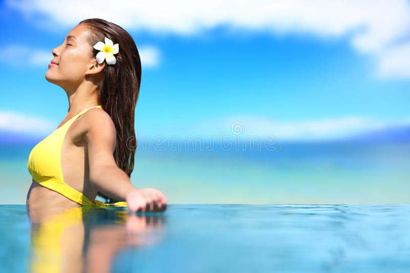 Relaxing serene woman at travel spa resort pool. Happy blissful asian young woman in bikini enjoying sun on holidays on Hawaii royalty free stock images