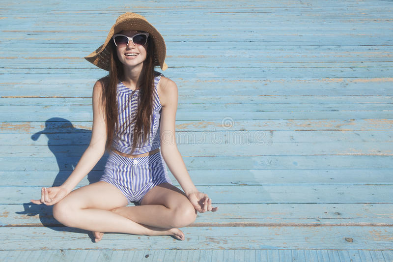 Relaxing Smiling girl on the beach. Yoga pose. Relaxing Smiling girl on the beach. Yong woman in the yoga lotus pose on the bright background royalty free stock photos
