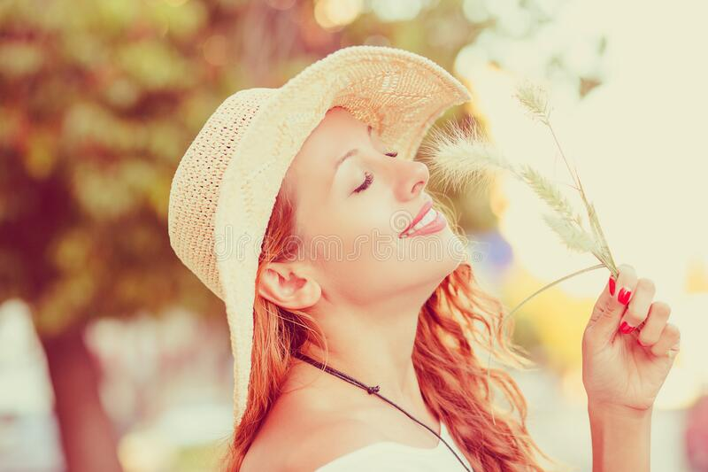 Relaxing and smiling. Woman breathing deeply eyes closed and enjoying the sun in a warmth park at sunset stock photography
