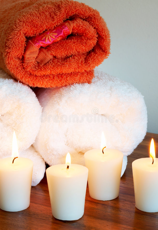 Relaxing spa scene with rolled up towels. Relaxing spa scene with white and orange rolled up body towels and burning candles royalty free stock photos