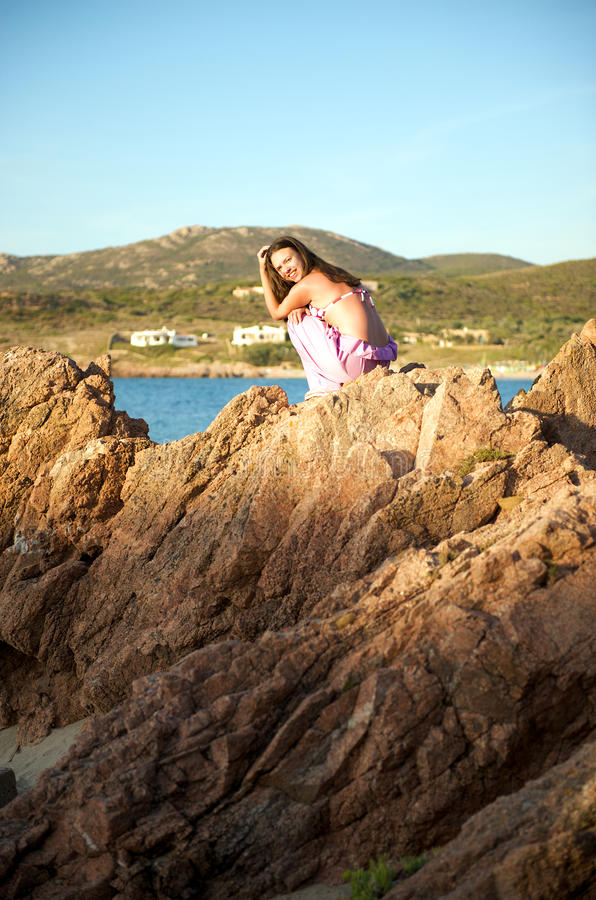 Relaxing at sunset time. Pretty woman relaxing duting her holiday on the beach royalty free stock image