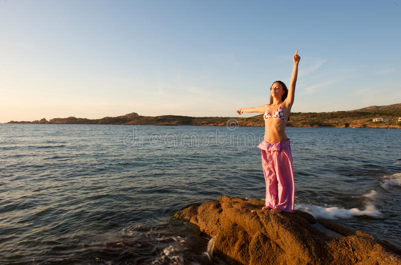 Relaxing at sunset time. Pretty woman relaxing duting her holiday on the beach royalty free stock photography
