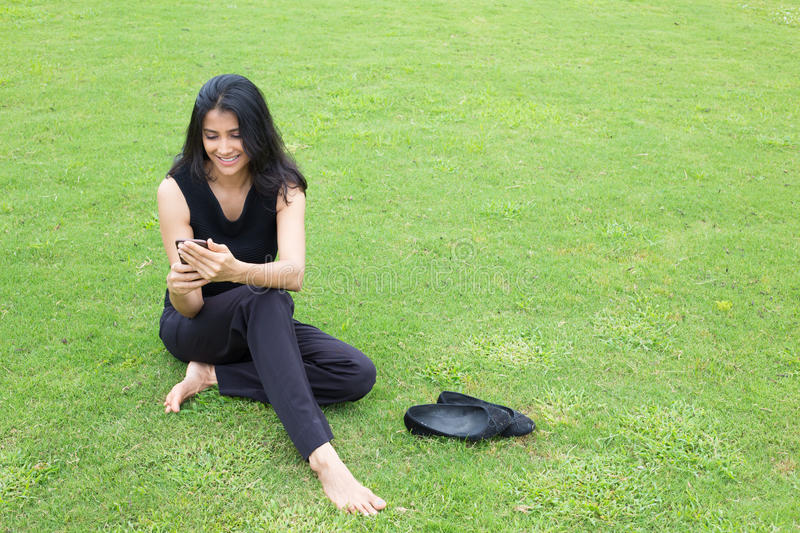 Relaxing and texting. Closeup portrait, young successful happy business woman in dark shirt, sitting on green grass checking her cellphone, isolated outside stock image