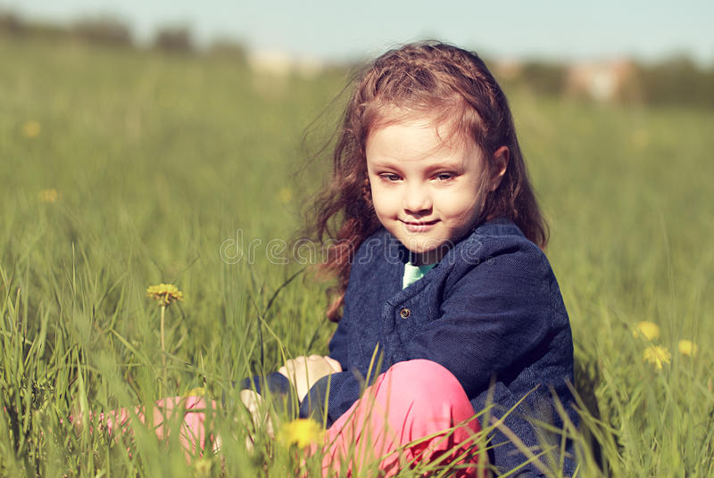 Relaxing thinking cute kid girl sitting in green grass in sunny. Summer day stock images