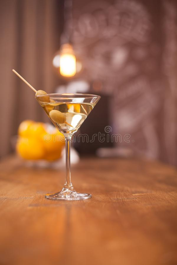 Relaxing time in restaurant with a glass of martini and green olives royalty free stock photo