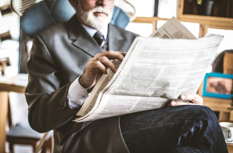 Relaxing time. Senior businessman riding newspaper. Close up image. Business senior person royalty free stock images