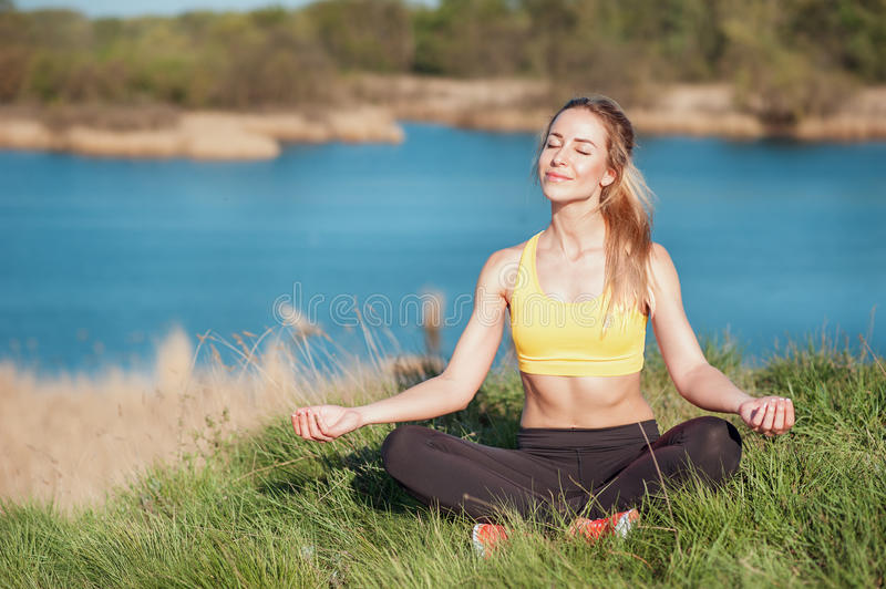 Relaxing after training. Attractive young girl in fashionable sportswear sitting in grass and doing meditation on beautiful natura. L river background. Woman royalty free stock photos