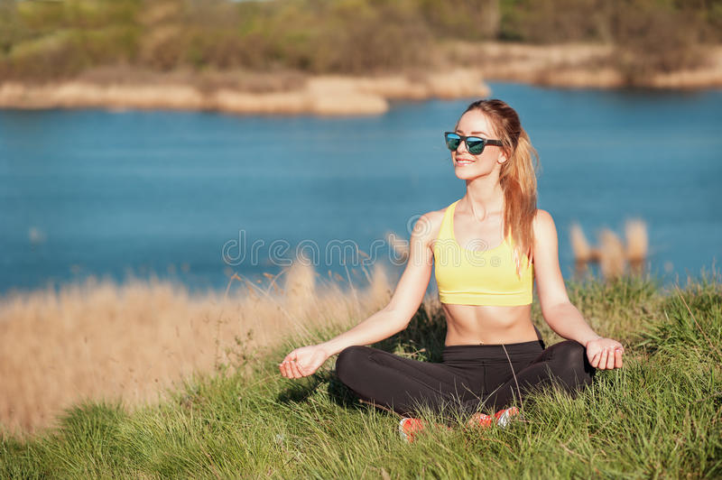Relaxing after training. Attractive young girl in fashionable sportwear and sunglasses sitting in grass and doing meditation on be. Autiful nature background royalty free stock images
