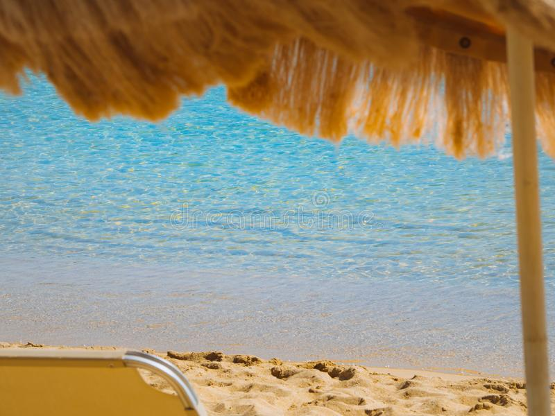 Relaxing view of the beautiful empty sand beach - beach chair and calm waters royalty free stock photos
