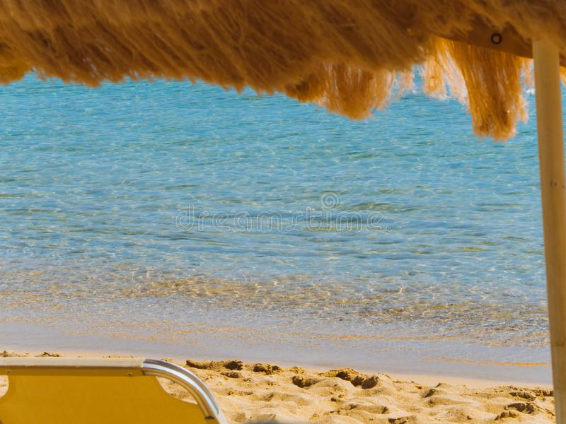 Relaxing view of the beautiful empty sand beach - beach chair and straw roof stock image