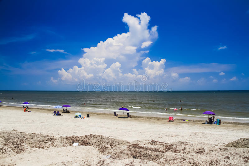 A Relaxing View of the Beautiful Galveston Beach with large Cloud. A Relaxing View of the Beautiful Galveston Beach with a large Cloud and People Lounging at royalty free stock photos