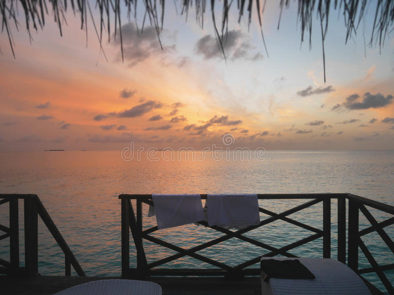 Relaxing view of open sea at dawn from Maldives resort`s water bungalow room window. Relaxing view of open sea at dawn from water bungalow room window. The stock images