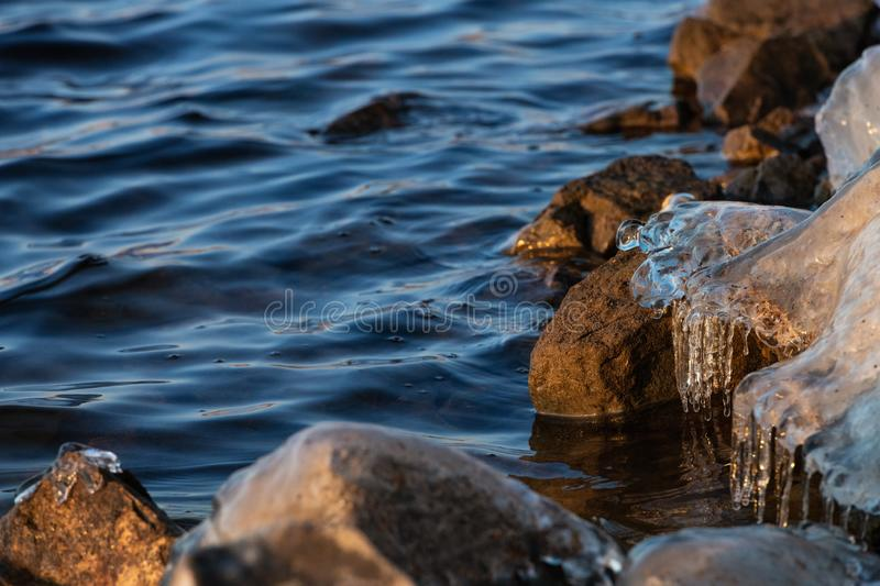 Relaxing view of a stones in the water with an ice cap at sunset stock images