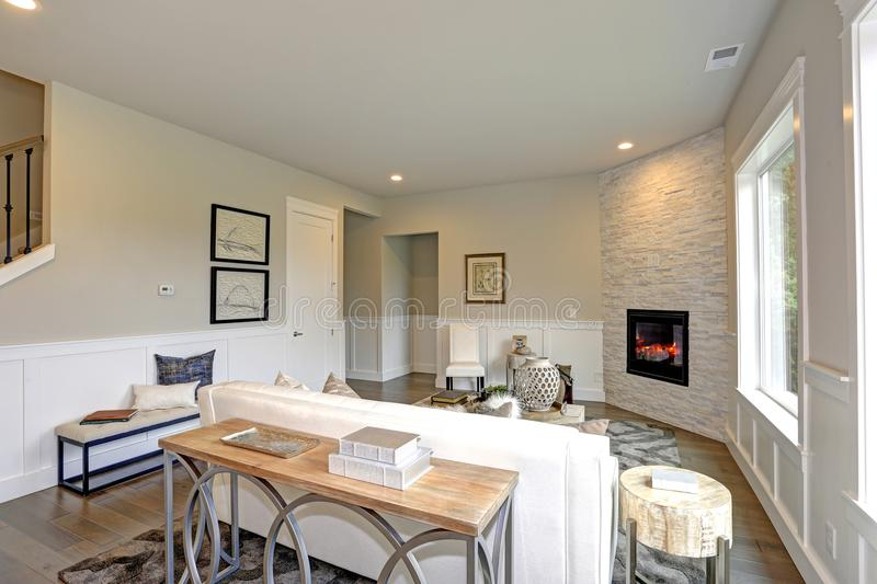Luxury living room features corner stone fireplace. Relaxing white living room in a luxury new construction home features corner stone fireplace lined with tan royalty free stock photos