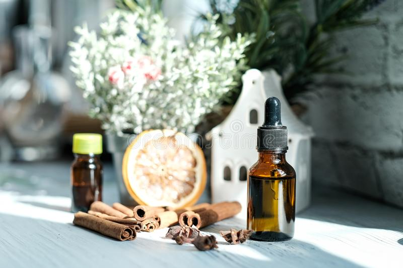 Relaxing winter season Essential oils blend. Dark glass bottles, cinnamon, orange, pine twigs, anise. royalty free stock photography