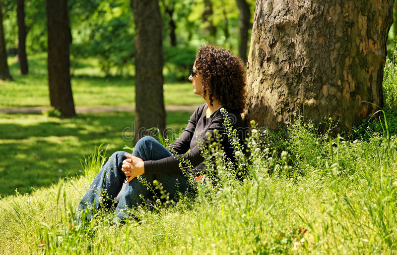 Relaxing woman. In the green park stock photography