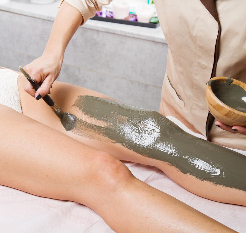relaxing woman lying on a massage table receiving a mud treatment stock image