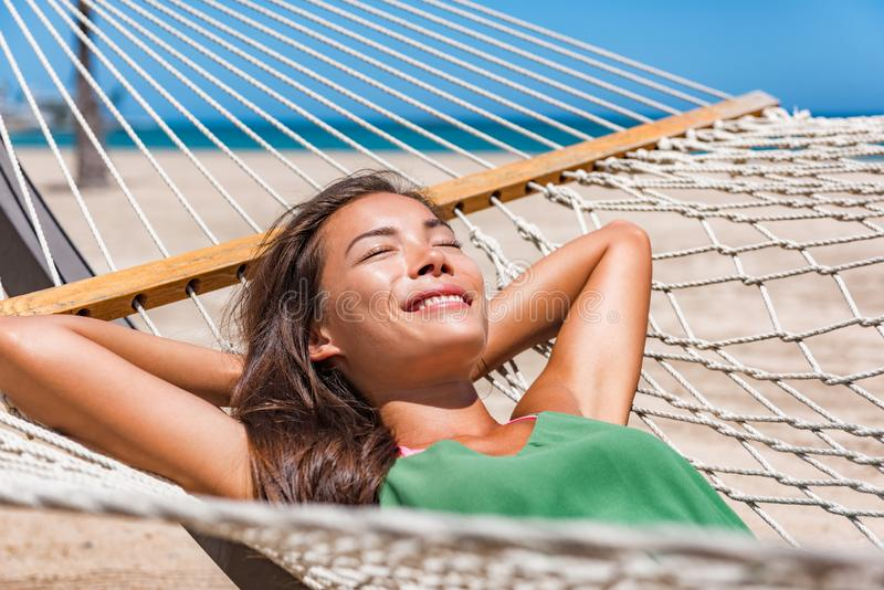 Relaxing woman sleeping on hammock in the tropical sun. Asian girl resting lying down in resort lounger laid back enjoying suntan. In Caribbean travel holidays royalty free stock image